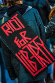 "Closeup of the Back of a protester Wearing a Sign Saying ""Riot — Stock Photo"
