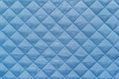Blue quilted synthetic fabric with grained texture — Stock Photo