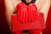 Mujer las manos en guantes rojos sosteniendo un embrague rojo — Foto de Stock