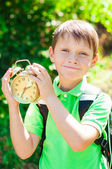 Boy with a backpack and a clock in hands — Stock fotografie