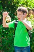 Boy with a backpack and a clock in hands — Stock Photo