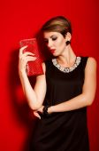 Beautiful girl with a red clutch bag — Foto Stock