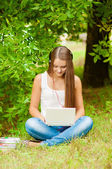 Teen girl works with the laptop on the grass — Foto Stock
