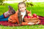 Little girl with apples in  park — Photo