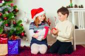 Children near a Christmas tree with gifts — Stock Photo