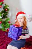 Little girl near the Christmas tree with gifts — Stock fotografie