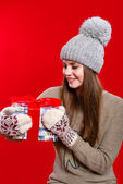 Young girl in hat and mittens with gift box — Stock Photo