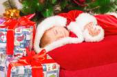 Baby in Santa costume sleeping at the Christmas tree — Stock Photo