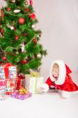 Baby in Santa costume at the Christmas tree with gifts — Stock Photo