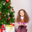 Little girl near the Christmas tree with gifts — Stock Photo #59798307