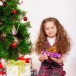 Little girl near the Christmas tree with gifts — Stock Photo #59840311