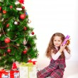 Little girl near the Christmas tree with gifts — Stock Photo #59849213