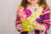 Handen van een klein meisje met Lentebloemen — Stockfoto
