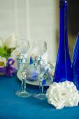 Bridal bouquet of blue iris white tulips glasses and bottles — Stock Photo