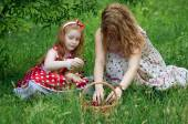 Mother and little girl with a basket of cherries — Stock Photo