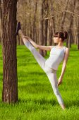 Young girl athlete doing stretching in a tree on the grass — Stock Photo