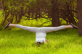 Young girl doing yoga on a green grass — Stockfoto