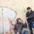 Two street hooligans or rappers standing against a graffiti pain — Stock Photo #58876255