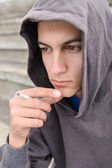 Young man in depression smoking a cigarette on a stadion. Concep — Stock Photo