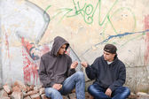 Two street hooligans or rappers standing against a graffiti pain — Stock Photo