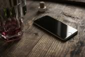 Smartphone on wooden table with whiskey — Stock Photo