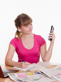 The girl dials a phone number on newspaper ad — Stock Photo