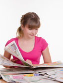 Girl thumbs through the newspaper to find right ads — Stock Photo
