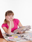 Girl sitting with a pile of newspapers at table — Stock Photo