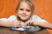The girl at table tinkering sand applique — Stock Photo