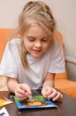 Five year old girl making sand applique — Stock Photo