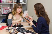Employee looks in the mirror on make-up consultation — Stock Photo
