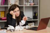 Sad girl in the office with a bunch of crumpled paper — Stock Photo
