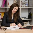 Female office worker grinning writing in a notebook for your desktop — Stock Photo #66124321
