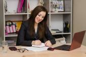 Female office worker grinning writing in a notebook for your desktop — Foto Stock