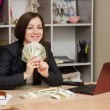 Girl behind desk office in front him holding a fan of money — Stock Photo #66130881