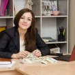 Постер, плакат: Office worker sitting at table with a bunch of money and looks in picture