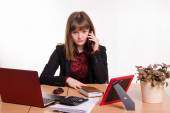 The girl behind office table talks on phone — Stock Photo