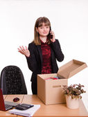 Girl in office collects personal belongings and calling on phone — Stock Photo