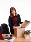 Dismissed girl in office near table collects personal belongings a box — Stock Photo