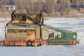 Burnt wooden structure standing on ice of river — Stock Photo