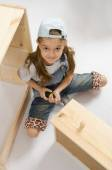 Little girl in overalls collector furniture spins screwdriver — Stock Photo
