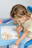 Six year old girl draws a paint something in the picture — Stock Photo