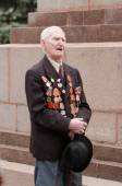 Portrait of a veteran on  background monument to fallen — Stock Photo
