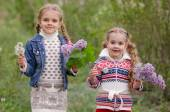 Two girls with dandelions and lilacs — Stock Photo