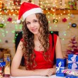 Beautiful girl sitting at a table with Christmas gifts — Stock Photo #75890533