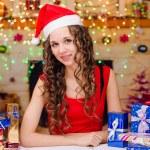 menina bonita sentada à mesa com os presentes de Natal — Fotografia Stock  #75890533