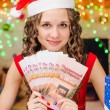 The girl is holding a Christmas gift certificates — Foto de Stock   #75934321