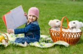 Happy girl showing the book on picnic — Stock Photo