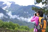 Woman photographer taking photo at plateau mountain peak — Stockfoto