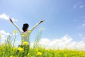 Cheering woman open arms at cole flower field — Stock Photo